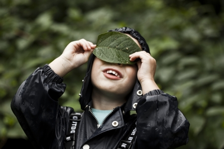 Boy hiding eyes and nose behind a leaf Stock Photo - 15980627