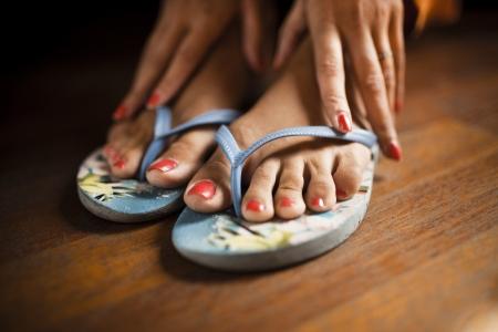 pies sexis: Pies descalzos con esmalte de uñas rojo en goma flip flops. Las manos tocando los pies