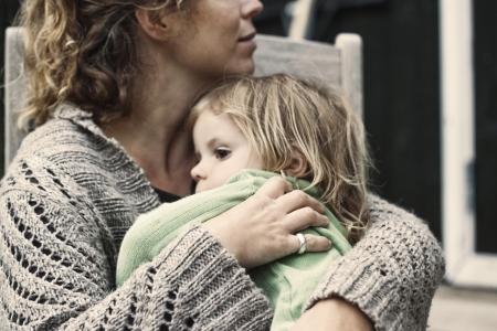 bambini tristi: Una madre che tiene sua figlia stanca