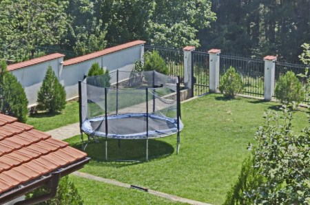 Jumping trampoline in green field at garden