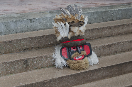 cultural artifacts:  Colourful theatrical mask of mummer sitting on the staircase