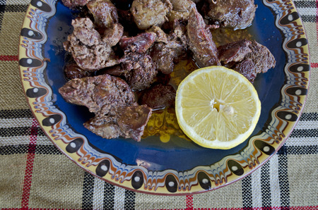 Portion of chicken liver roasted with butter and shorn lemon in the clay dinner-plate