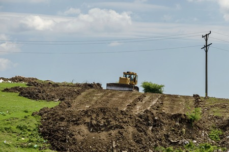 waste products: Bulldozer  bury garbage at rubbish dump in the field, Ludogorie, Bulgaria Stock Photo