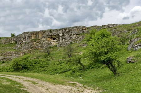 crevice: General view toward sedimentary rock with cave in the field, Ludogorie, Bulgaria Stock Photo