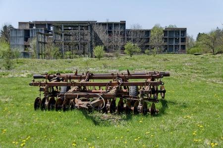 harrow: Abandoned unfinished building and farm machinery, harrow, Bulgaria Stock Photo
