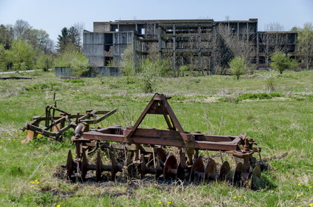harrow: Abandoned unfinished building and farm machinery, harrow, plough,  Bulgaria