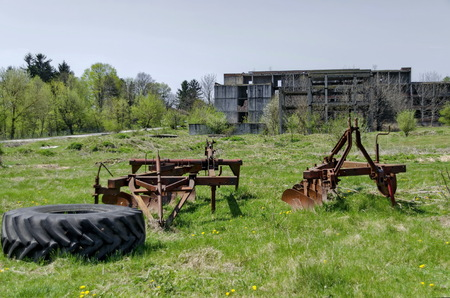 unfinished building: Abandoned unfinished building and farm machinery, plough, Bulgaria