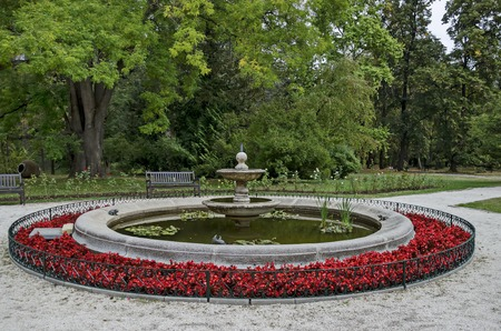 Beautiful autumnal venerable forest with fountain and flower in National monument of landscape architecture Park museum Vrana in former time royal palace on the outskirts of Sofia, Bulgaria, Europe