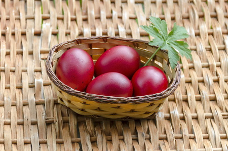 Closeup paint Easter red eggs in the basket on wicker table, Sofia, Bulgaria Stock Photo