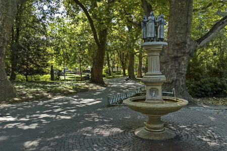 Beauty fountain  with lady among venerable sycamore in public garden of Plovdiv town, Bulgaria, Europe