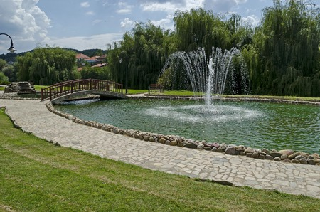 View of public garden with beauty artificial pond, fountain and bridge, town Delchevo among Maleshevo and Osogovo mountains, Macedonia, Europe
