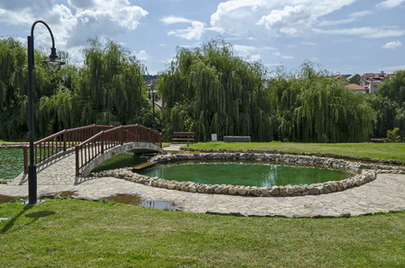 View of public garden with beauty artificial pond and bridge, town Delchevo among Maleshevo and Osogovo mountains, Macedonia, Europe Archivio Fotografico