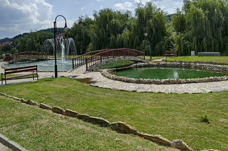 General view of public garden  in  residential district with artificial pond, fountain and  bridge, town Delchevo, Macedonia, Europe Archivio Fotografico