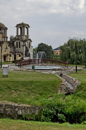 General view of public garden  in  residential district with new orthodox church, artificial ponds, fountain and bridges, town Delchevo, Macedonia, Europe