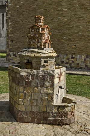 Fountain  with miniature of  orthodox church at the back in public garden, town Delchevo , Macedonia, Europe