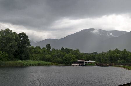 A view of a artificial lake with shelter and boats on a rainy day in rila park near town Dupnitsa, Bulgaria Foto de archivo - 129724977