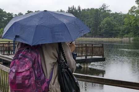 Rainy day walk with umbrellas in Rila Park near town Dupnitsa, Bulgaria Foto de archivo - 129724986