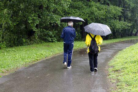 Rainy day walk with umbrellas in Rila Park near town Dupnitsa, Bulgaria Foto de archivo - 129725301