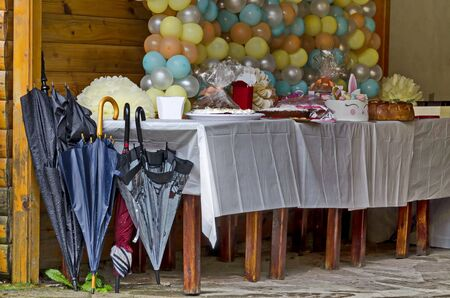 Outdoor party  in Rila Park decorated with colorful balloons, cake and gifts on a rainy day near Dupnitsa, Bulgaria Foto de archivo - 129725332