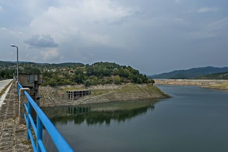 View from Topolnitsa dam, lake or barrage on the river Topolnitsa, part from village Muhovo and reservoir wall, Ihtiman region, Bulgaria, Europe