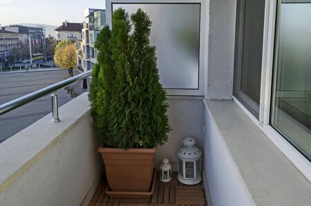 Balcony of a new apartment with  cypress flower in pot and lamp, town Kazanlak, Bulgaria Фото со стока