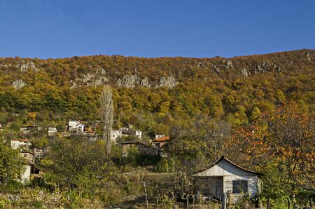 Amazing autumn view of glade, hill, forest with deciduous trees and residential district of the pretty village Zhrebichko, Bratsigovo municipality,  Rhodope mountains, Bulgaria