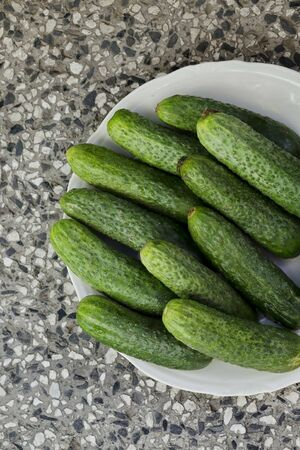 A stack of several fresh green cucumber gherkins in a plate, Sofia, Bulgaria