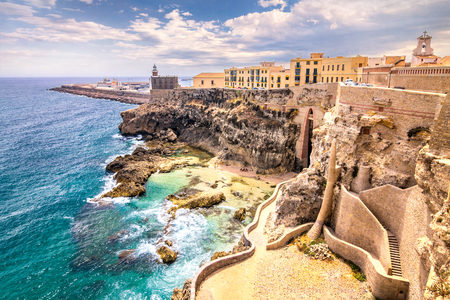 City walls, lighthouse and harbor in Melilla, Spanish province in Morocco. The rocky coast of the Mediterranean Sea. Stock Photo