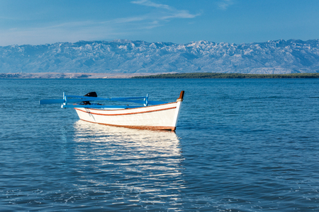 A white boat at sea. The national park Paklenica of Croatia in the background, southern slopes of Velebit mountain, Europe. Stock Photo