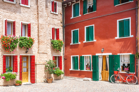 Colorful facade of an old house with a bicycle in the small Italian town of Caorle, Europe.
