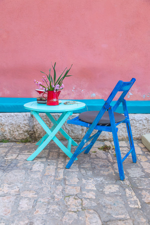 Still life with table and chair at the old color facade of the house, Rovinj, Croatia, Europe. Stock Photo