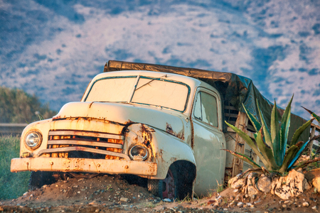 The wreck of an old rusty truck in the countryside. Banco de Imagens