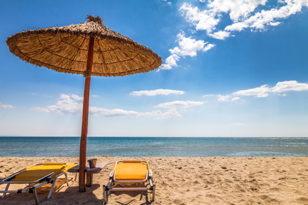 A straw umbrella with deck chairs on a sandy beach by the sea. The Paralia, a tourist seaside part of the municipality Katerini, Greece, Europe. Stock Photo