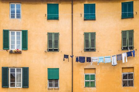 Facade of an old house with hanging washed laundry in Lucca town, in an ancient city in the Tuscany region of Italy, Europe.