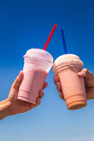 Milkshakes held in hands on background of blue sky in sunny day.