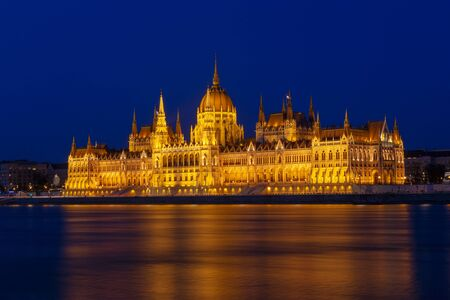 The Hungarian Parliament Building, a notable landmark of Hungary in Budapest. View of the main facade illuminated above the Danube river. Long exposure at a blue hour after sunset. Stockfoto