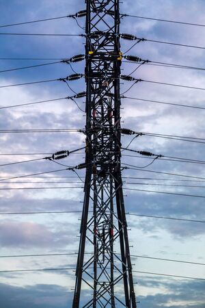 High voltage power line pylons at sunset. 写真素材