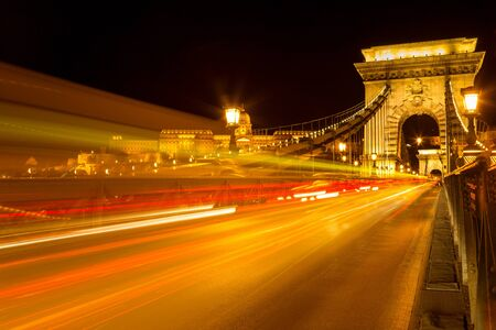 The famous Széchenyi Chain Bridge in Budapest with the Buda Castle at a background, Hungary. Long exposure with light trails of cars at a night.