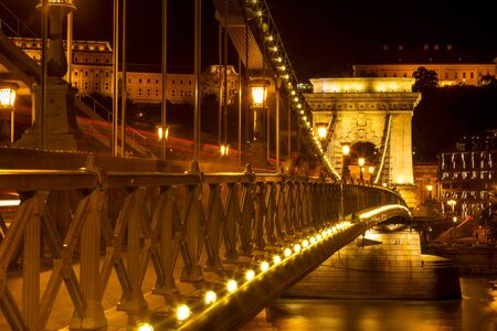 The famous Széchenyi Chain Bridge in Budapest, Hungary, illuminated above the Danube river. Long exposure with light trails of cars at a night. Stockfoto