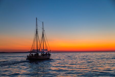 Sunset with silhouette of sailboat on the Adriatic sea near Zadar town, Croatia, Europe.
