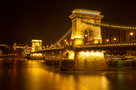 The famous Széchenyi Chain Bridge in Budapest, Hungary, illuminated above the Danube river. Long exposure with light trails of cars at a night. Redactioneel