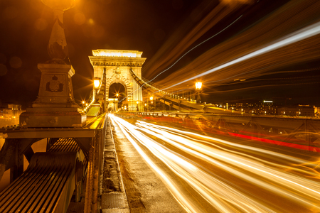 The famous Széchenyi Chain Bridge in Budapest, Hungary. Long exposure with light trails of cars at a night. Redactioneel
