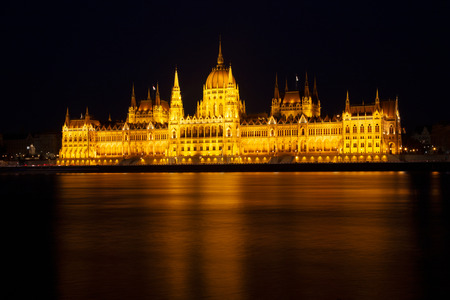 The Hungarian Parliament Building, a notable landmark of Hungary in Budapest. View of the main facade illuminated above the Danube river. Long exposure at a night.