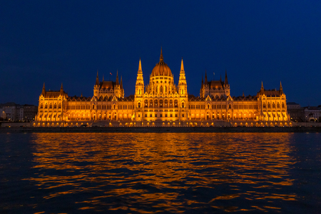 The Hungarian Parliament Building, a notable landmark of Hungary in Budapest. View of the main facade illuminated above the Danube river at night. Redactioneel