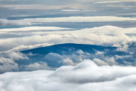 Landscape with peaks of hills in the clouds.