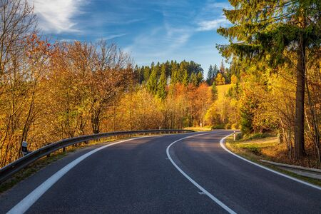 A turn on the road through the autumn landscape around the forests. Stockfoto