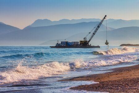 Sea digger adjusting pebble coast.
