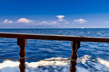 View of the sea through the wooden railing of a cruise ship.