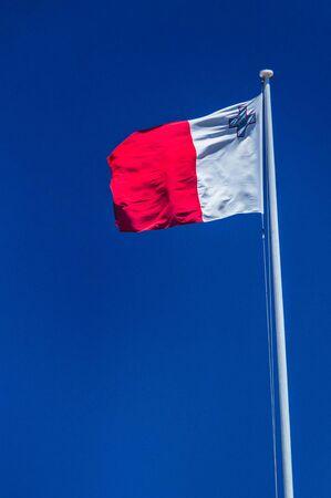 Flag of Malta on flagpole.