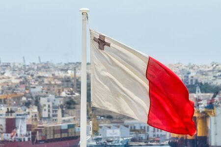 Flag of Malta on flagpole with cityscape in the background.